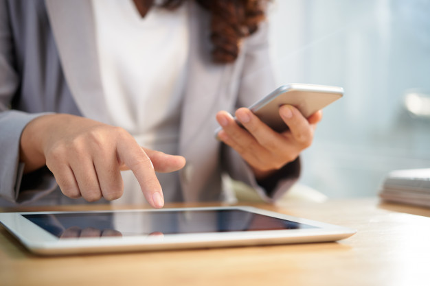 mulher trabalhando com tablet e celular em transformação digital